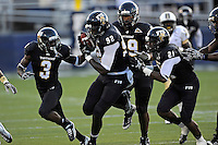 17 September 2011:  FIU defensive line Paul Crawford (92), surrounded by defensive back Richard Leonard (3), defensive line Isame Faciane (99), and defensive back Chuck Grace (21), takes a fumble recovery to the end zone in the first quarter as the FIU Golden Panthers defeated the University of Central Florida Golden Knights, 17-10, at FIU Stadium in Miami, Florida.  Officials later negated the fumble.