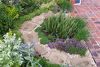 Herbs growing: rosemary, thymes in bloom, with comfrey, brick patio, circular stone pathway with footprints inset