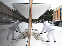 Doyle Mayfield with Weber Painting is reflected in a window as he clears the entrance way of a building on Arlington Boulevard Thursday after a snowfall in Charlottesville, VA. Photo/Andrew Shurtleff
