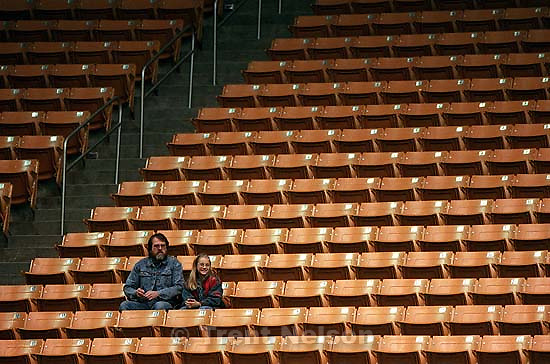 Man and girl in empty stands at BYU vs Utah women's basketball. BYU won.<br />