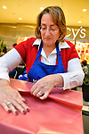 Dec. 12, 2012 - Garden City, New York, U.S. - EILEEN GONZALEZ, of Northport, helps the Merrick Kiwanis Club, a community service group, gift wrap presents at Roosevelt Field mall in Long Island to raise funds to use for charity, during the busy winter holiday shopping season. She was one of several members of Meadowbrook Women's Initiative who helped out at the booth. Some ways Kiwanis helps the community are by providing food, clothing, and school supplies to those in need, sending children to Kamp Kiwanis, providing scholarships and hosting a Harvest Ball for senior citizens.