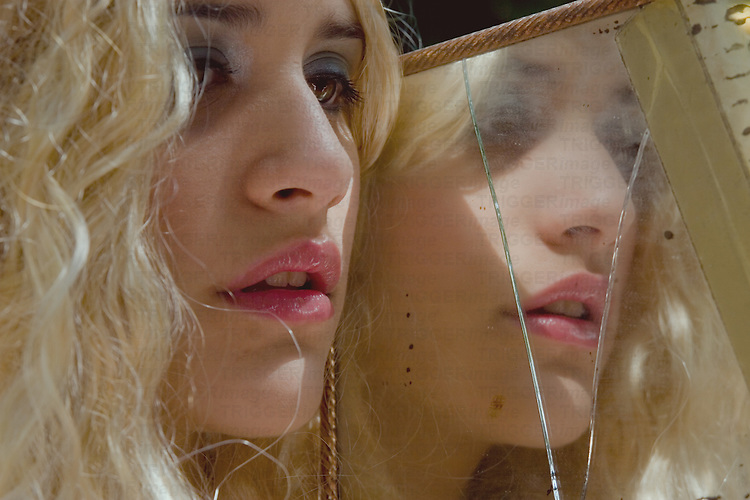 Close up of female teenagers face with blonde hair beside cracked mirror