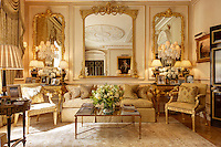 A luxurious sitting room with gilt mirrors and gilded furniture. The room is furnished in neutral tones.