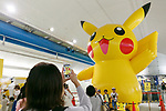 A woman takes pictures of a huge Pikachu on display at Minatomirai Station on August 9, 2017, Yokohama, Japan. Hundreds of Pokemon GO app fans gathered at the special Pokemon GO PARK, a 2km area including special PokeStops and PokemonGyms, to collect characters. Minatomirai holds an annual Pokemon event including a parade of 1500 Pikachu through the area and this year has added Pokemon GO attractions. Pokemon GO PARK is open from August 9 to 15. (Photo by Rodrigo Reyes Marin/AFLO)