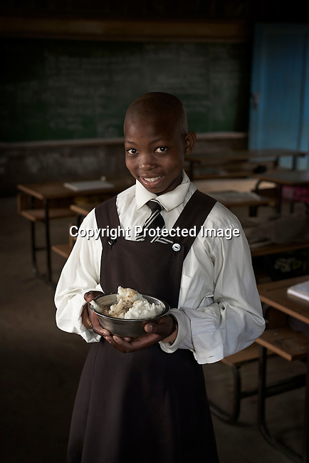 MASERU, LESOTHO SEPTEMBER 1: A girl holds her lunch box in a classroom at Masapong primary school on September 1 in Masapong district outside Maseru, Lesotho. The are given two meals a day, usually pap and fish by the World Food Program (WFP).  (Photo by: Per-Anders Pettersson)