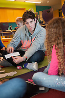 Salve Regina volunteer Jake Williams, '15, helps children on their language skills at the Pell School in Newport as part of a Modern Languages Program.