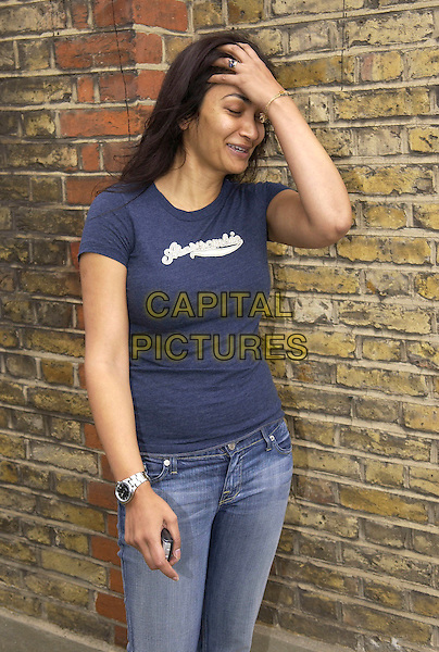 FARIA ALAM.Outside her Surrey Home.August 20th, 2005.blue t-shirt t shirt half length touching head laughing.www.capitalpictures.com.sales@capitalpictures.com.© Capital Pictures.