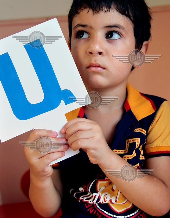 A boy holds the letter A in class during a session at the Inclusive preschool No. 92.