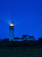 Lighthouse casts guiding light into dark blue night, Truro, Cape Cod, Massachusetts, USA