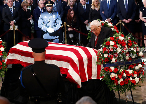 Former U.S. Secretary of State Henry Kissinger kneels at the casket of late U.S. Senator John McCain during ceremonies honoring McCain inside the U.S. Capitol Rotunda in Washington, U.S., August 31, 2018. REUTERS/Kevin Lamarque