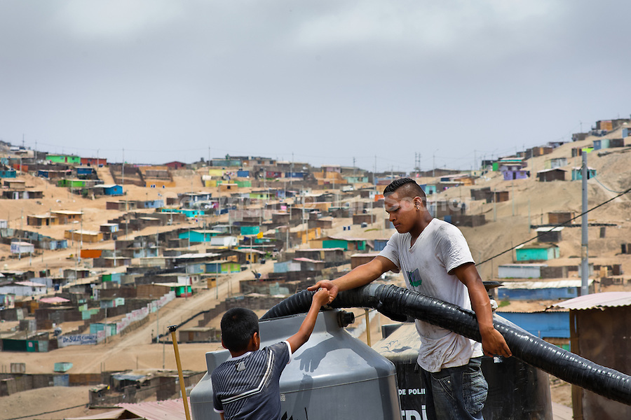 A Peruvian boy pays a water distribution worker to fill a tank with drinking water on the dusty hillside of Pachacútec, a desert suburb of Lima, Peru, 22 January 2015. Although Latin America (as a whole) is blessed with an abundance of fresh water, having 20% of global water resources in the the Amazon Basin and the highest annual rainfall of any region in the world, an estimated 50-70 million Latin Americans (one-tenth of the continent's population) lack access to safe water and 100 million people have no access to any safe sanitation. Complicated geographical conditions (mainly on the Pacific coast), unregulated industrialization (causing environmental pollution) and massive urban poverty, combined with deep social inequality, have caused a severe water supply shortage in many Latin American regions.