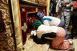 Africans Christian pilgrims look to a 14-point silver star on the marble floor of the Grotto in the Church of the Nativity, believed to be the birthplace of Jesus Christ, in the West Bank city of Bethlehem on December 22, 2016. Photo by Wisam Hashlamoun