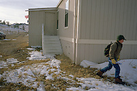 Joe Kennedy, 13, the lone student at Cozy Hollow Elementary School on the Kennedy ranch in Wyoming, leaves the trailer that serves as school and teacher's residence. Wyoming, one of the nation's most rural states, supports many isolated schools with few students. (Kevin Moloney for the New York Times)