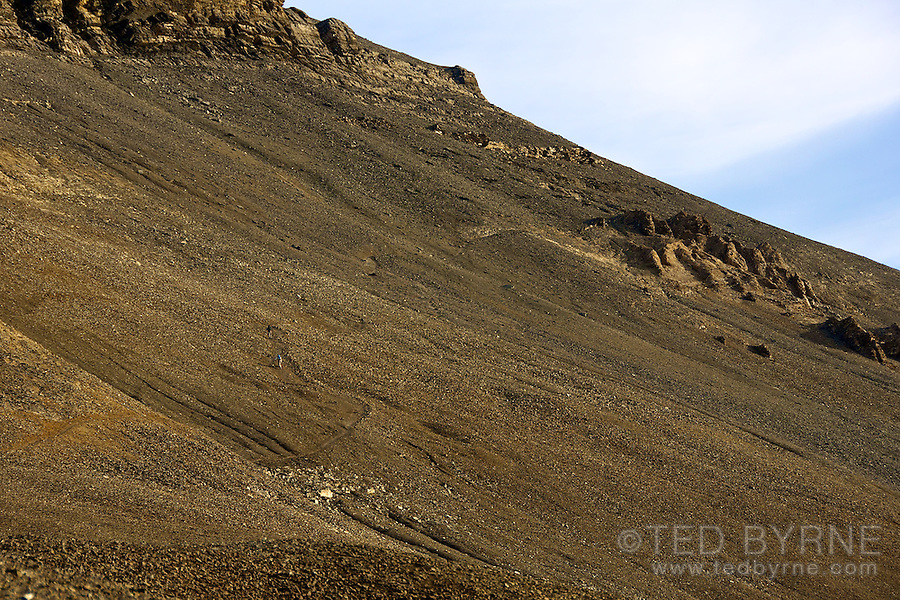 Two hikers ascending a slope of scree in the Swiss Alps