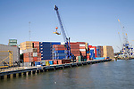 Crane and colourful containers stacked on quayside, Port of Rotterdam, Netherlands