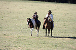 A cowboy and his son out on the range to round up cattle