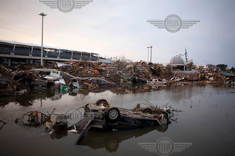 Overturned cars near extensive debris at Sendai airport. On 11 March 2011 a magnitude 9 earthquake struck 130 km off the coast of Northern Japan causing a massive Tsunami that swept across the coast of Northern Honshu. The earthquake and tsunami caused extensive damage and loss of life.