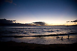children play in the surf at last light. Sunset at Kaanapali Beach on Maui, Hawaii