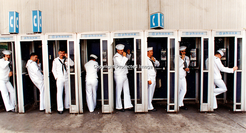 Sailors just off the carrier USS Carl Vinson hit the phone booths at Naval Air Station Alameda. .(1993 photo by Ron Riesterer)