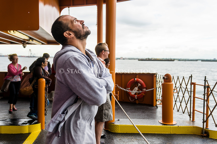 Staten Island, NY - 23 Aug 2014 - Man taking in a refreshing harbor breeze on the Staten Island Ferry