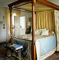The guest bedroom has a wooden four-poster bed with hangings by Colefax and Fowler