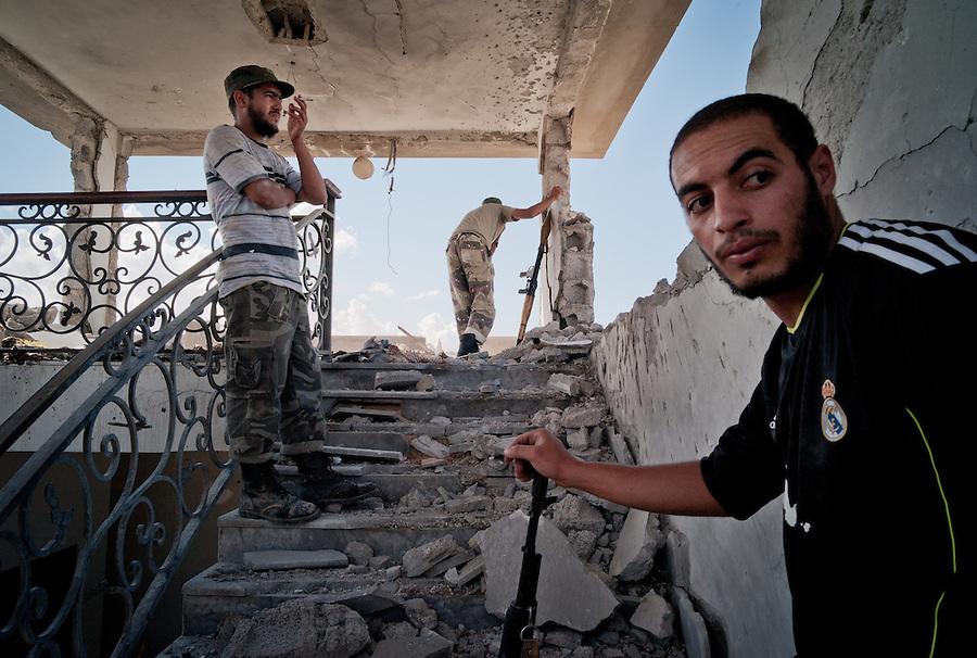 Anti-Gaddafi fighters survey Gaddafi loyalist positions in Sirte, Libya.