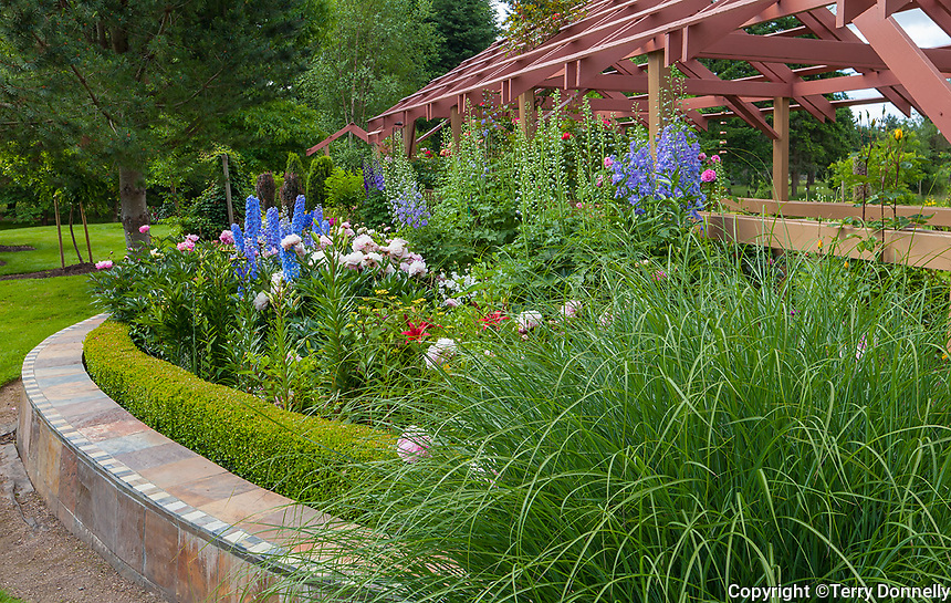 Vashon Island, WA: Curved flower bed with rose pergola with colorful blooms of peonies and delphiniums in Froggsong garden in summer