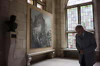 An elderly man walks past a painting which shows German forces burning down Leuven University Library during World War I at the library of Leuven University in Leuven, Flemish Brabant, Belgium, August 25, 2014. 2014 marks 100th anniversary of the Great War.