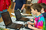 Garden City, New York, USA. 19th May 2013. Two young boys use remote control type devices to fly airplanes in simulated flight on laptop computers at Annual Flying Model Show sponsored by Academy of Model Aeronautics (AMA) and Model Airplane Clubs of Nassau, Suffolk & Queens, in the lobby of the Cradle of Aviation Museum.