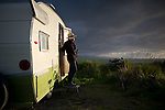 Teri Lowe poses with her Shasta trailer on hte Homer Spit awaiting the Burning Basket ceremony in Homer, Alaska. 140914.