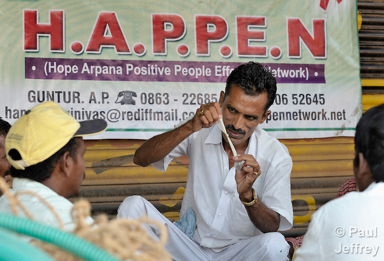 Srinivas Rao, a HIV positive leader of the Hope Arpana Positive People Effective Network, conducts an educational session for laborers in Guntur, Andhra Pradesh, India, explaining HIV and its prevention, including the proper use of condoms, which he demonstrates. (Note Special Instructions below.)