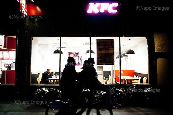 Man at KFC watching the couple on the bike, central London, May 2012..(Photo by Piotr Malecki / Napo Images..Londynie, mezczyzna siedzie w KFC i przyglada sie mlodym ludziom jadacym razem na rowerze..Maj 2012.Fot: Piotr Malecki / Napo Images