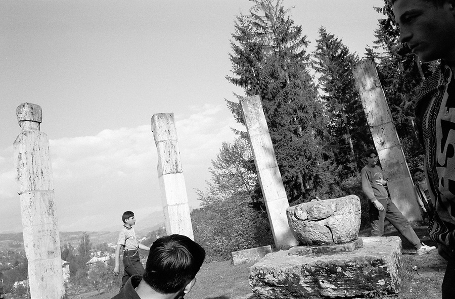ROMANIA / Maramures / Moisei / May 2000..Youth gather around a monument commemorating a massacre by retreating Hungarian troops in October 1944 which killed 29 villagers. The stone pillars were sculpted by Romanian sculptor Vida Geza...© Davin Ellicson / Anzenberger..