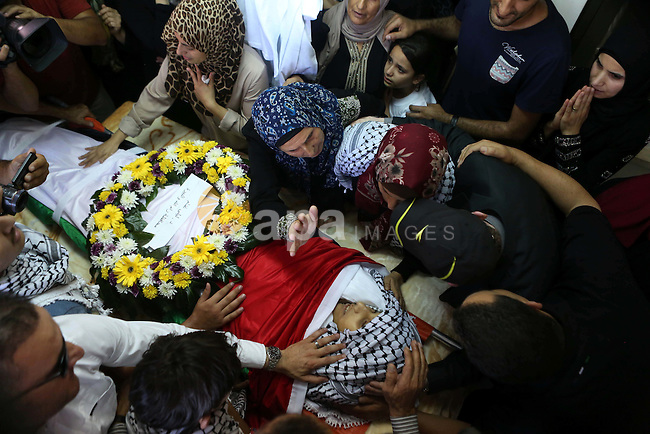 The mother of Palestinian boy Mahmoud Badran, 15, who was killed by Israeli troops on Tuesday, kisses his body during his funeral in the village of Beit Ore-Tahta near the West Bank city of Ramallah June 23, 2016. Photo by Shadi Hatem