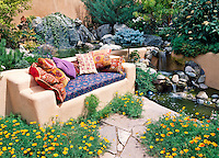 Susan Blevins of Taos, New Mexico, created this southwestern garden scene with a waterfall, an adobe banco and some colorful cushions and pillows.