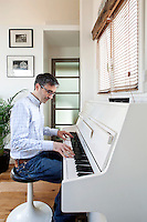 Gregory Gauthier photographed at the piano in his Paris apartment