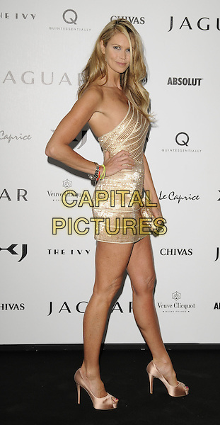 ELLE MacPHERSON.The New Jaguar XJ launch party, Saatchi Gallery, Duke of York's HQ, London, England. .July 9th, 2009 .full length gold beige sequins seqinued one shoulder dress clutch bag silk satin peep toe platform christian louboutin shoes heels hand on hip.CAP/CAN.©Can Nguyen/Capital Pictures.