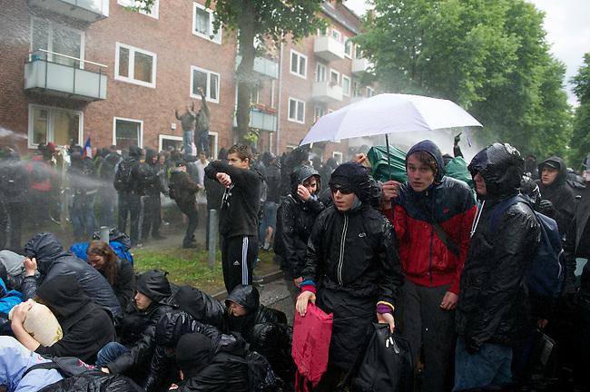 5-6000 Menschen protestierten am Samstag den 2. Juni 2012 im Hamburger Stadtteil Wandsbeck gegen einen Aufmarsch von Neonazis der sog. Freien Kameradschaften und Autonomen Nationalisten.<br /> Die geplante Demonstrationsroute der Neonazis wurde durch Sitzblockaden und Barrikaden blockiert. An mehreren Stellen wurden Muelltonnen in Brand gesetzt. Die Polizei ging mit Wasserwerfern, Schlagstoecken und CS-Gas/Pfefferspray gegen die Demonstranten vor.<br /> Nach mehreren Stunden Verspa?tung wurden die Neonazis auf einer geaenderten Route durch den Stadtteil gefuehrt. Gegendemonstranten wurden mit massivem Polizeieinsatz von Route entfernt. Dabei kam es zu etlichen Verletzten.<br /> Im Bild: Eine Sitzblockade wird von der Polizei mitt Wasserwerfern beschossen.<br /> 2.6.2012, Hamburg<br /> Copyright: Christian-Ditsch.de<br /> [Inhaltsveraendernde Manipulation des Fotos nur nach ausdruecklicher Genehmigung des Fotografen. Vereinbarungen ueber Abtretung von Persoenlichkeitsrechten/Model Release der abgebildeten Person/Personen liegen nicht vor. NO MODEL RELEASE! Nur fuer Redaktionelle Zwecke. Don't publish without copyright Christian-Ditsch.de, Veroeffentlichung nur mit Fotografennennung, sowie gegen Honorar, MwSt. und Beleg. Konto: I N G - D i B a, IBAN DE58500105175400192269, BIC INGDDEFFXXX, Kontakt: post@christian-ditsch.de<br /> Bei der Bearbeitung der Dateiinformationen darf die Urheberkennzeichnung in den EXIF- und  IPTC-Daten nicht entfernt werden, diese sind in digitalen Medien nach &sect;95c UrhG rechtlich geschuetzt. Der Urhebervermerk wird gemaess &sect;13 UrhG verlangt.]