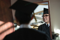 Aviation Management major Myeongjun Kim has a look in the mirror in his cap and gown before having his graduation photo taken during Grad Fair at UAA's campus bookstore.