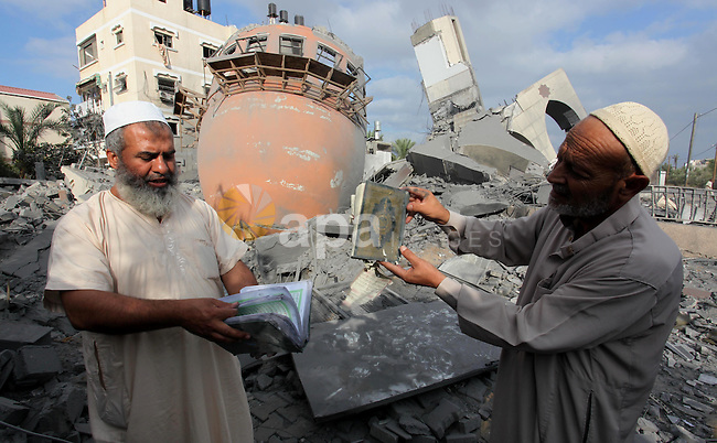 Palestinian men react in front of the remains of a mosque, which witnesses said was destroyed in an Israeli air strike before a 72-hour truce, in Khan Younis in the southern Gaza Strip August 11, 2014. Israeli negotiators were due in Cairo on Monday for talks on ending a month-old Gaza war with Palestinian militants, an Israeli government official said, after a new 72-hour truce brokered by Egypt appeared to be holding. Photo by Ramadan El-Agha