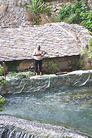 A man standing on a dam making a bowing gesture. The source of the Buna river and the house of the Whirling Dervishes, an old Muslim monastery, Blagaj. Federation Bosne i Hercegovine. Bosnia Herzegovina, Europe.