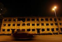Una macchina percorre di notte una strada con ancora evidenti i segni della guerra che sconvolse i balcani agli inizi degli anni 90.