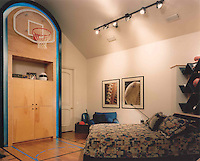 This lucky young man's bedroom sports a teal basketball court done up in his favorite teams colors. The cabinet hides electronics, the unique headboard echoes the Cubist-inspired bed ensemble. <br />