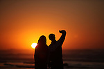 Palestinians take a selfie on the beach of Gaza City, during the last sunset of 2016, on December 31, 2016. Photo by Ashraf Amra