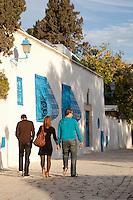 Three people walking along street, Sidi Bou Said, Tunisia