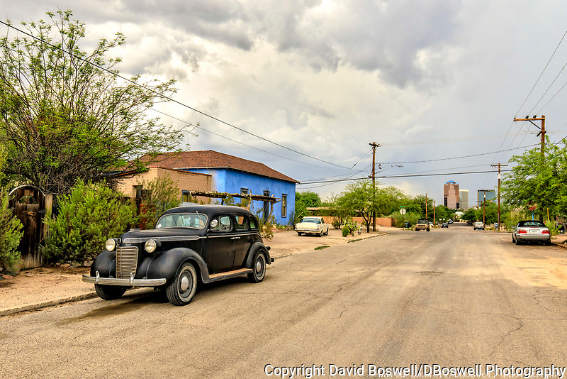 The modern skyline of downtown Tucson contrasts with the old homes and, in this case, cars of the the barrios South of downtown.