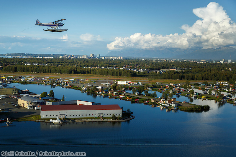 Super Cub float plane flies over Lake Hood with Anchorage, Alaska skyline and Chugach Mountains in background.   summer   MR/PR<br />