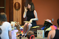NWA Democrat-Gazette/DAVID GOTTSCHALK Rachel Smith, children's librarian at the Fayetteville Public Library, demonstrates Tuesday, July 9, 2019, the proper way to hold your pinky while sipping tea during the Morning Buttons and Bows Tea Party at the library. Children, ages three to five, listened to tea party themed books, dressed in an assortment of dresses and button down shirts and enjoyed music while dining on fresh fruit, crumpets, quiche and goldfish crackers during the tea.