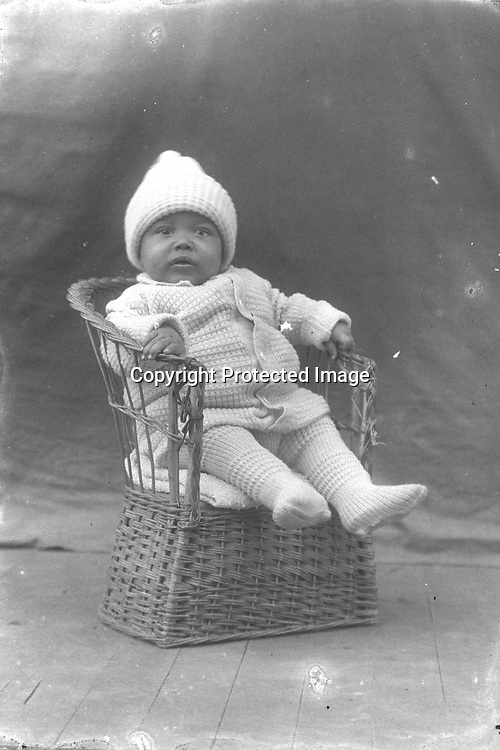 BABY IN A WICKER CHAIR. The chair is woven and the baby's outfit is knit, from head to toe.<br /> <br /> Photographs taken on black and white glass negatives by African American photographer(s) John Johnson and Earl McWilliams from 1910 to 1925 in Lincoln, Nebraska. Douglas Keister has 280 5x7 glass negatives taken by these photographers. Larger scans available on request.