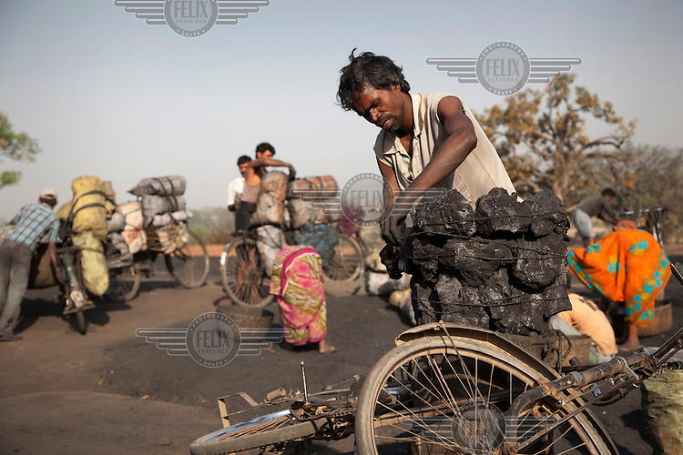 Men load their bicycles with coal at a small non-mechanized mine before undertaking a two-day trek to bring the coal to market. The work pays about 500 rupees (GBP 7.40) which is shared with their underground digging team and others. They must also pay bribes to local police to enable them to continue what is officially an illegal activity..